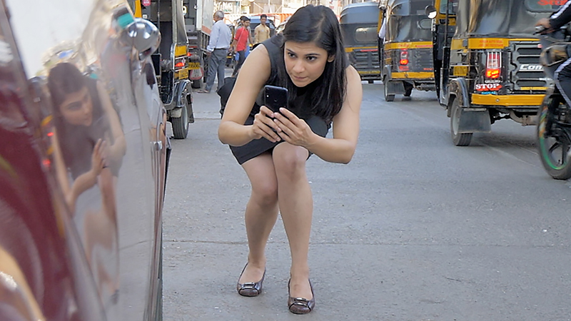 A girl clicking closeup picture of a car