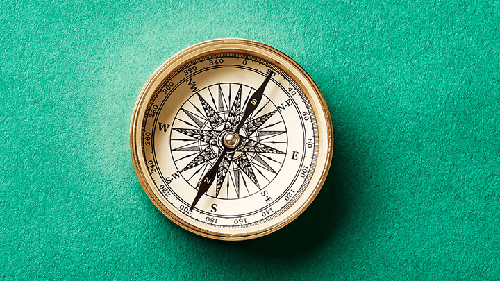 Compass on green background
