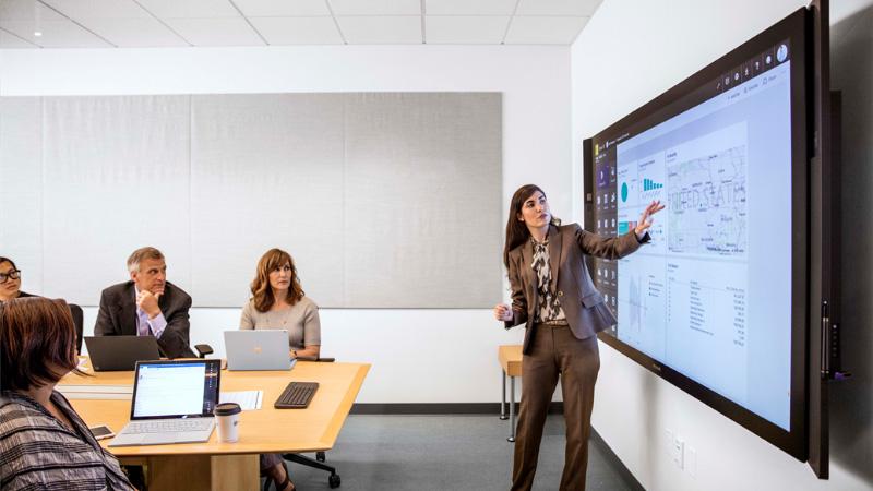 Γυναίκες παρουσιάζουν δεδομένα μπροστά από ένα Surface Hub σε μια σύσκεψη
