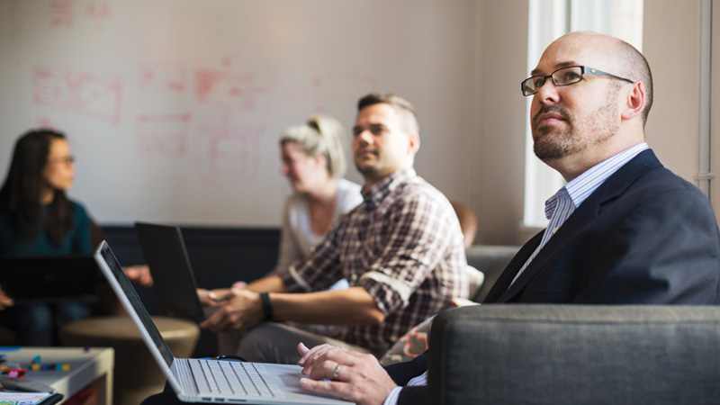 Ένας επιχειρηματίας ακούει κάτι μπροστά από έναν φορητό υπολογιστή