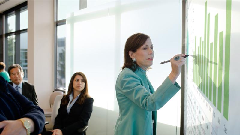 Μια γυναίκα εργάζεται σε ένα Surface Hub μπροστά σε ένα ακροατήριο