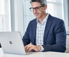 Ένας άντρας με σακάκι εργάζεται σε έναν φορητό υπολογιστή