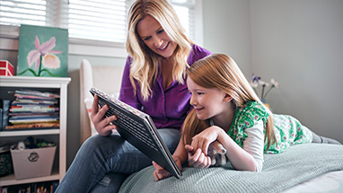 A woman looking at a Windows 10 PC with her daughter