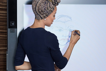Lady drawing/writing notes on Surface Hub whiteboard