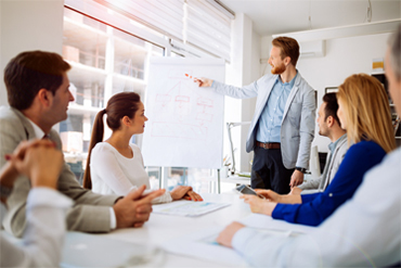 People in a meeting room with person pointing at whiteboard