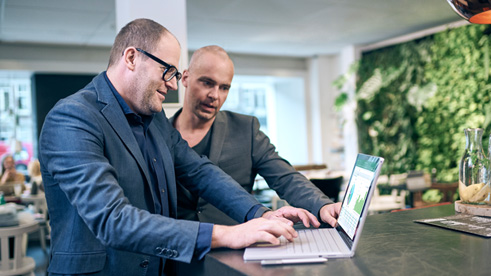 Two business men in discussion while working on a laptop