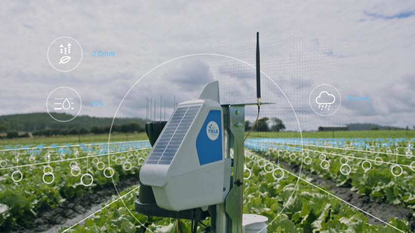 The Yield device in a farm with digital icons of a cloud, a water drop, and a leaf around it.