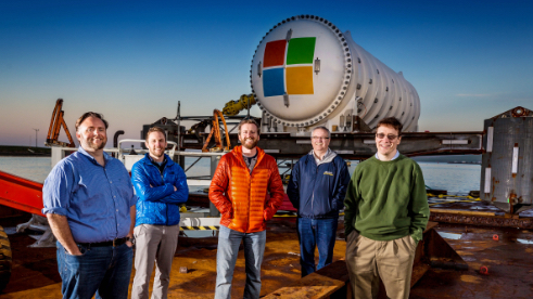 Project Natick team stands in front of an underwater container with the Microsoft logo on it.