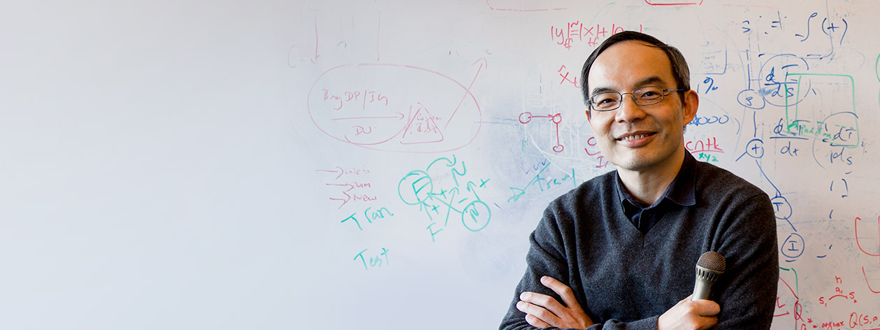Microsoft speech researcher, Xuedong Huang, stands in front of a whiteboard.
