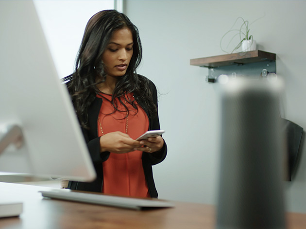 Young woman using a cell phone while standing before a computer