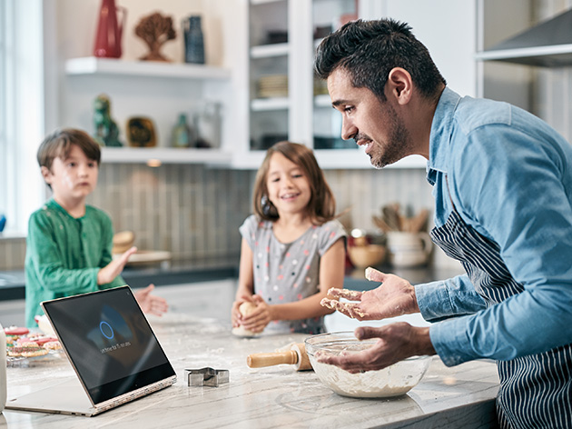 A father at home with his children using a digital device