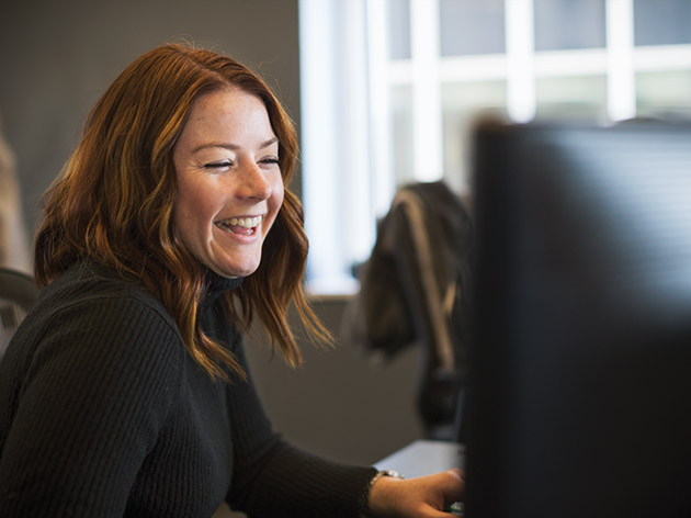 Woman laughing while looking at her computer screen