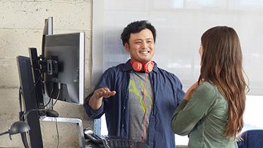 Ein Mann und eine Frau stehen vor zwei Bildschirmen und unterhalten sich
