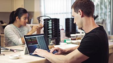 Ein Mann arbeitet an Daten an einem Surface und im Hintergrund arbeitet eine Frau an einem technischen Gerät.
