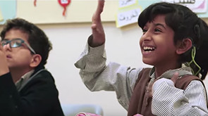 Smiling girl raises hand in classroom while boy looks on
