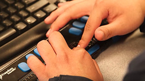 Close-up of hands interacting with assistive keyboard device