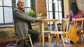 Smiling man sitting at table in indoor cafe