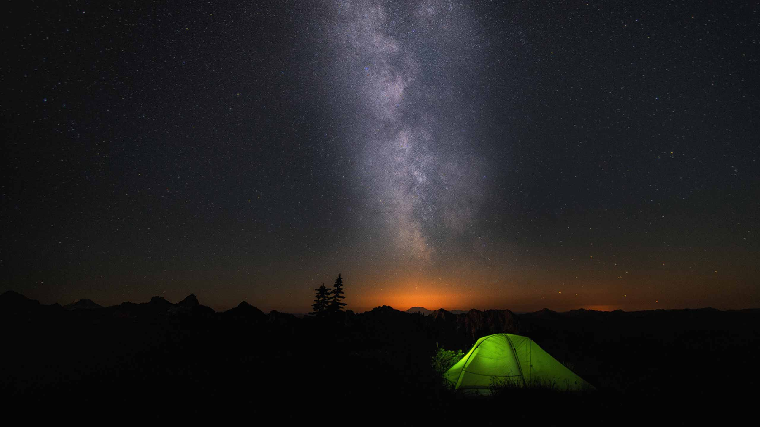 A green tent below the Milky Way in a dark night sky