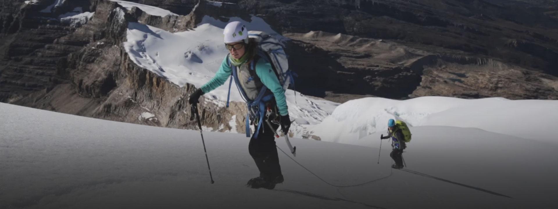 Woman climbing snowy mountain, learn about 50 Peak Challenge