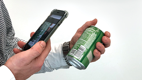 A person using a smartphone to read a barcode on a soda can
