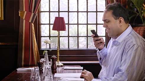 ALT TEXT A man sitting at restaurant and looking at his phone