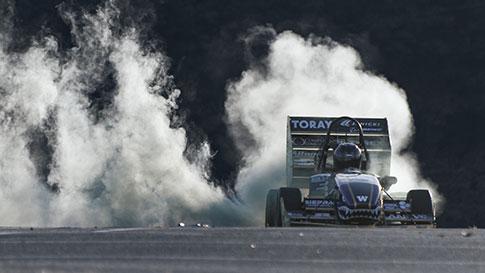 Formula type racecar spinning its wheels and smoke rising behind it