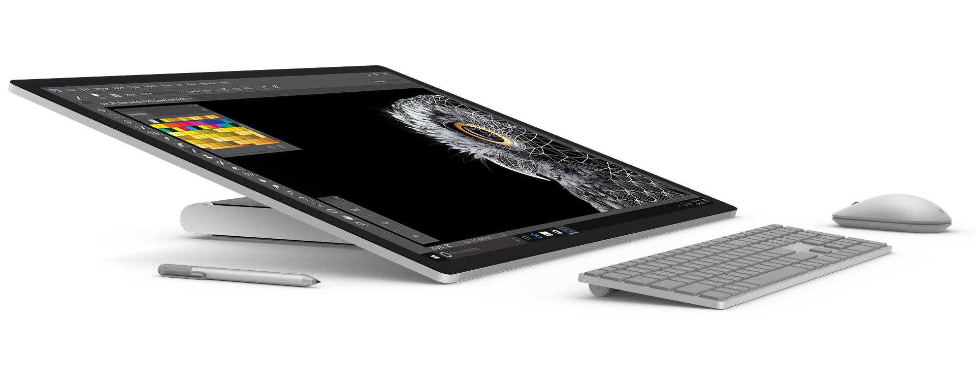 Surface Studio laid flat in studio mode, facing right with Surface Pen and Surface Keyboard & Surface mouse in front of it