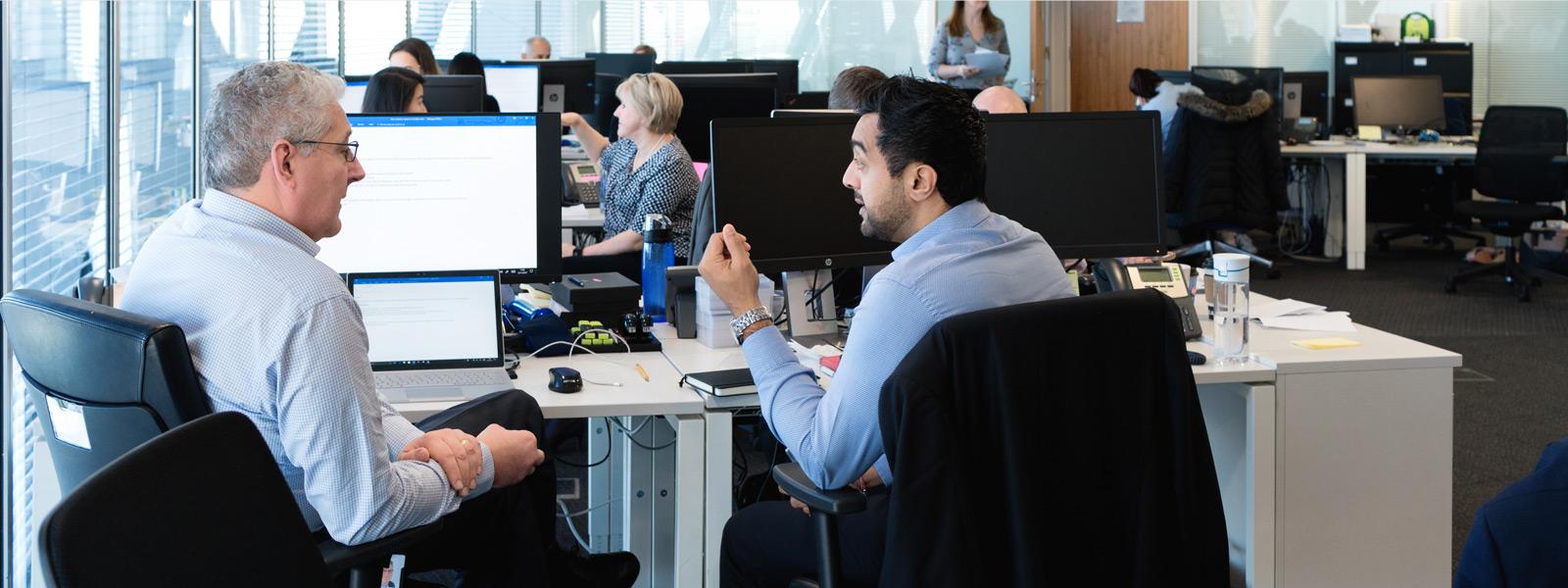 Two men talking at a desk