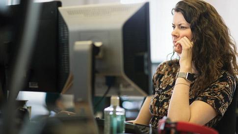 A woman looking at her desktop screen