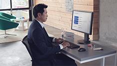 Businessman typing at a desktop computer