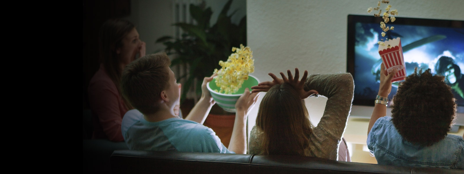 People sitting on couch watching a movie.