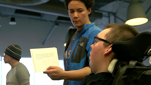Play Video, A man in a wheelchair and a woman collaborate using inclusive design activity cards.