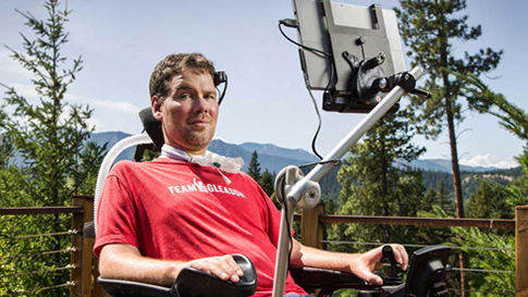 A man sits in his wheelchair against an evergreen and mountain backdrop.