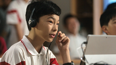 Play Video, A boy wears a headset and interacts with Skype on his laptop.