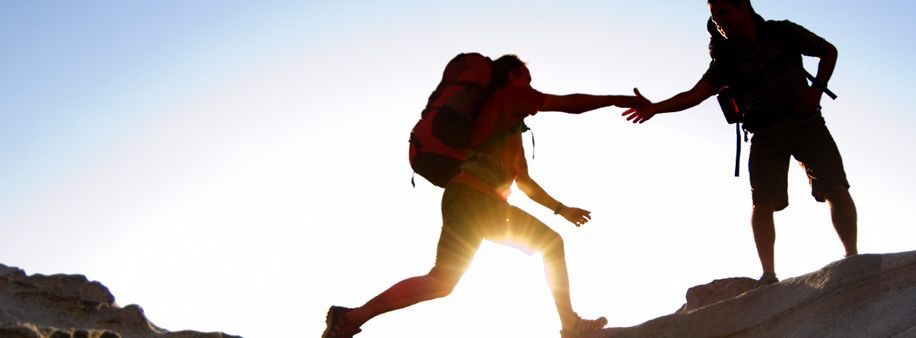 Image of a mountain climber reaching out to assist another climber reach the summit.