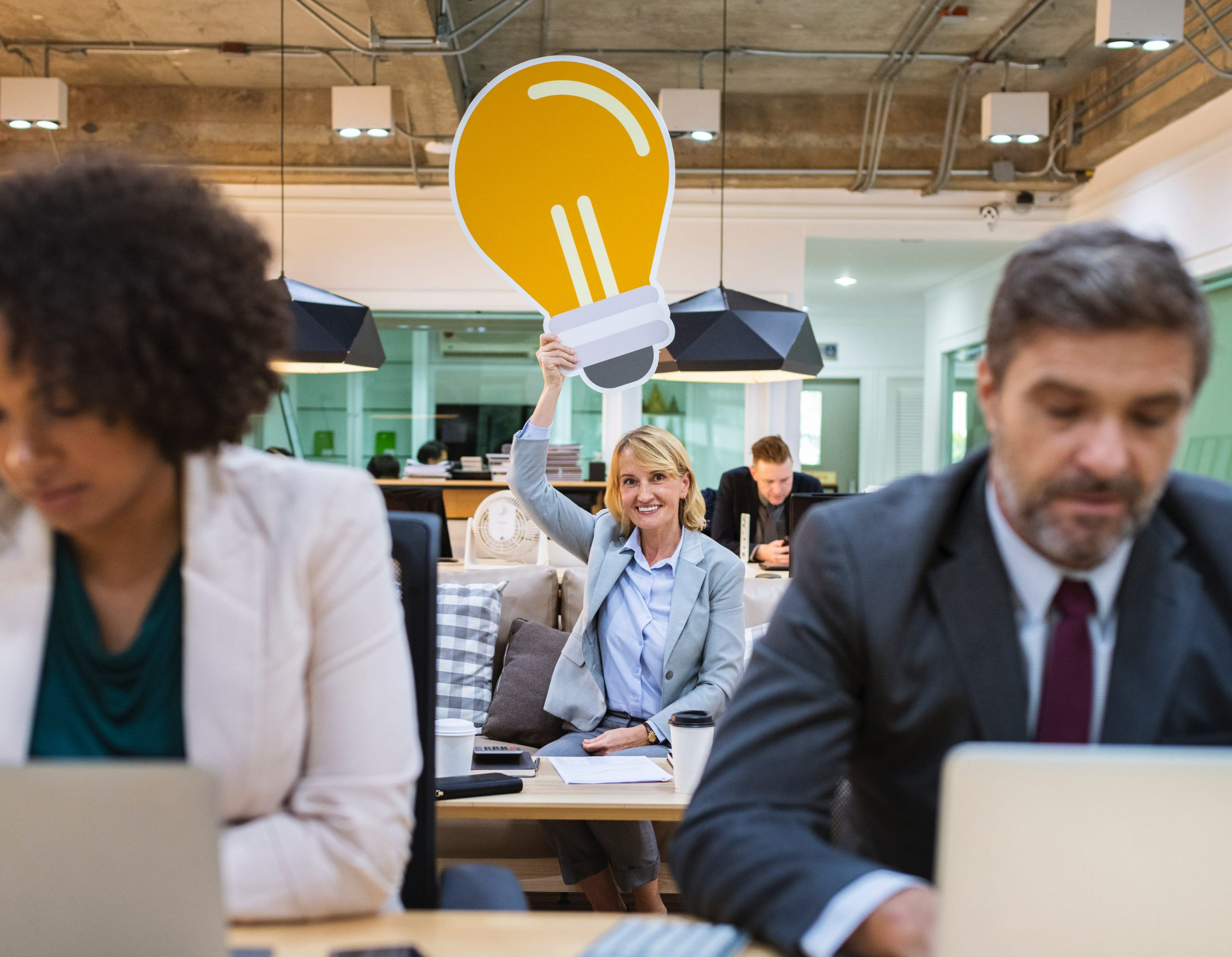 Busy business office with woman in middle holding lightbulb sign over her head.