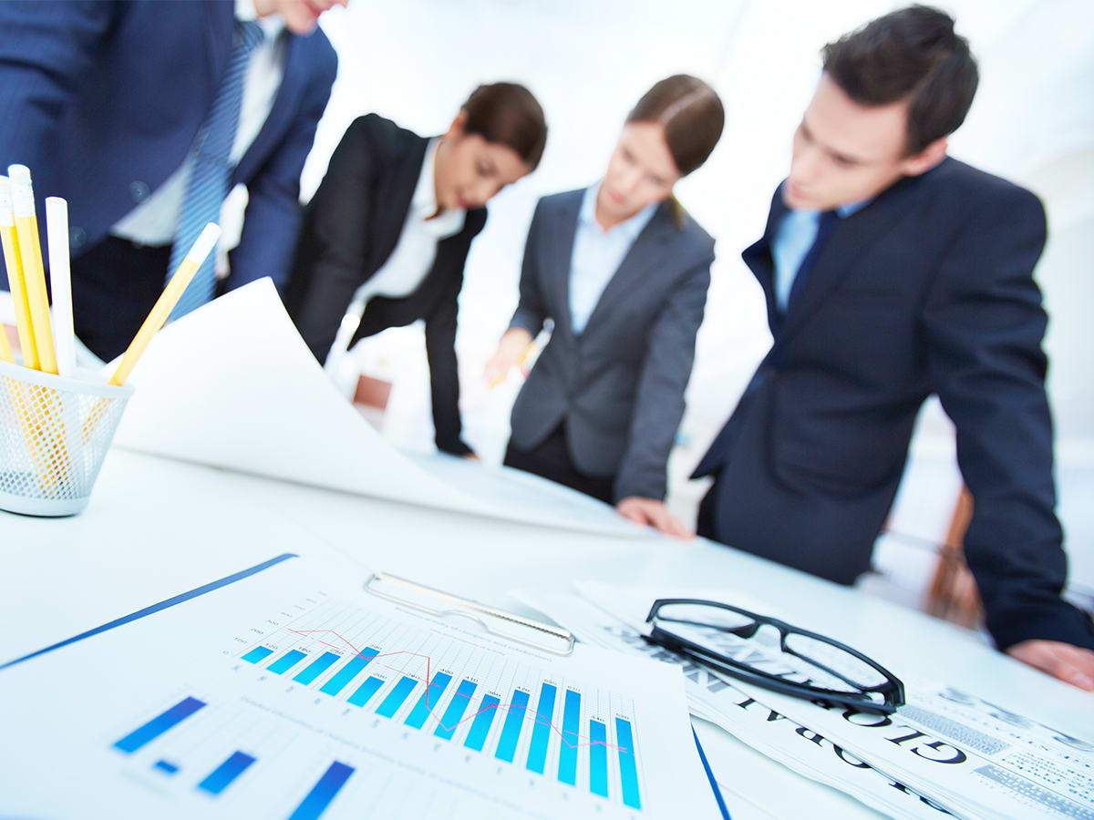 Business people working at table with graphs laid out