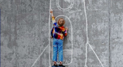 Child drawing a space ship larger than themselves on concrete with chalk