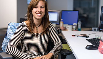 Caucasian woman sitting at desk in striped shirt