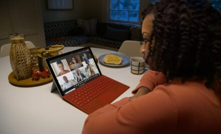 Image for: Over the shoulder photo of an adult female in kitchen participating in a Microsoft Teams video call on a Surface Pro with Poppy Red type cover.