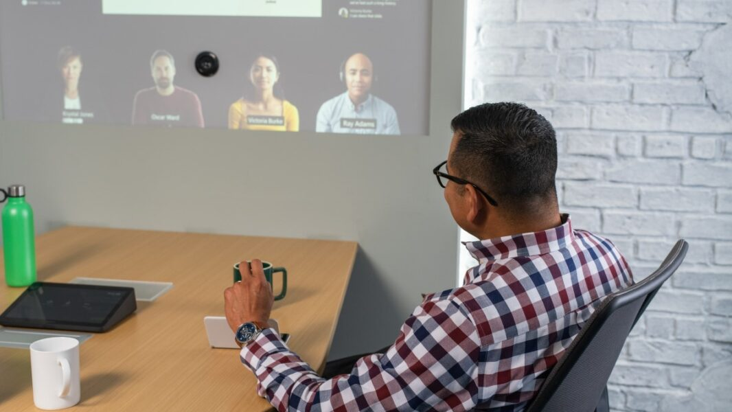 Adult male sitting at conference table looking at screen projected on wall.