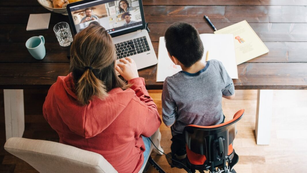High angle view of mother and son with disabilities watching video on laptop while sitting at home