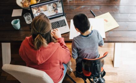 Image for: High angle view of mother and son with disabilities watching video on laptop while sitting at home