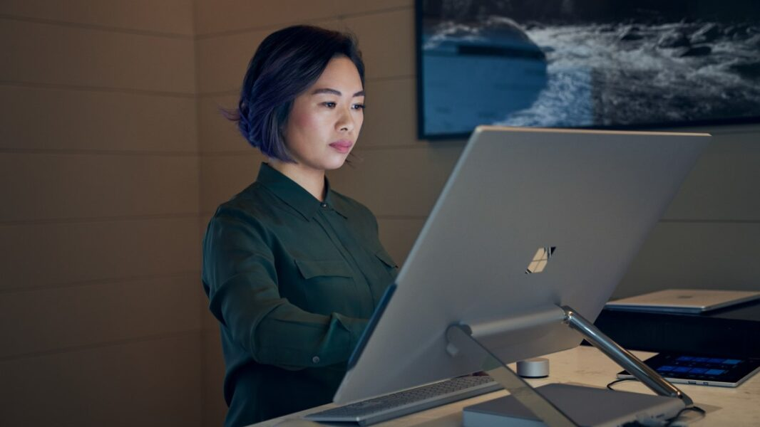 Side profile of a woman wearing a dark shirt in a dim office working on a Microsoft Surface Studio.