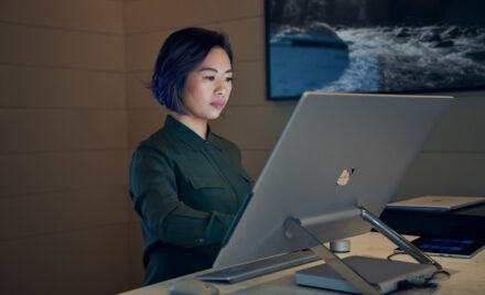 Image for: Side profile of a woman wearing a dark shirt in a dim office working on a Microsoft Surface Studio.