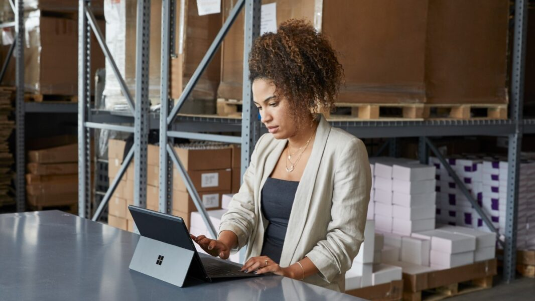 Adult female in a warehouse setting, sitting at a table using a platinum Microsoft Surface Pro X in laptop mode.