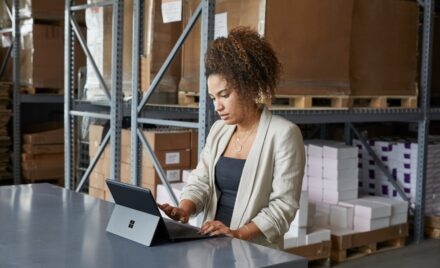 Image for: Adult female in a warehouse setting, sitting at a table using a platinum Microsoft Surface Pro X in laptop mode.
