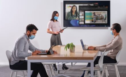 Image for: Coworkers setting up a PowerPoint presentation for a Microsoft Teams meeting in a conference room.