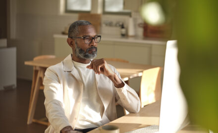 Image for: Man sitting at wooden table looking at the the screen on a desktop computer.