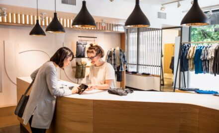 Image for: Female employee holding tablet for female consumer to sign and approve purchase. They are standing on either side of a retail clothing store checkout counter.